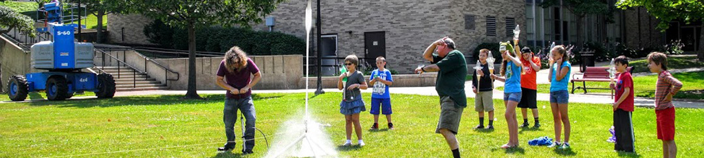 Young students watch a water rocket blast off