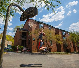 Student playing basketball outside townhouses
