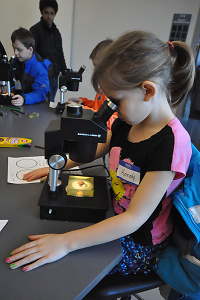 Elementary student looking in a microscope
