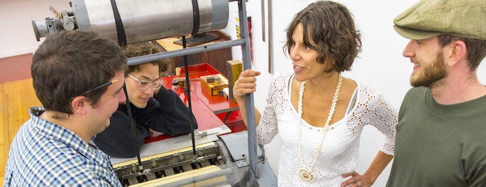 Professor talking to students next to a printing press