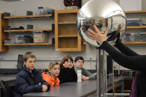 Professor holding metal sphere for sixth graders