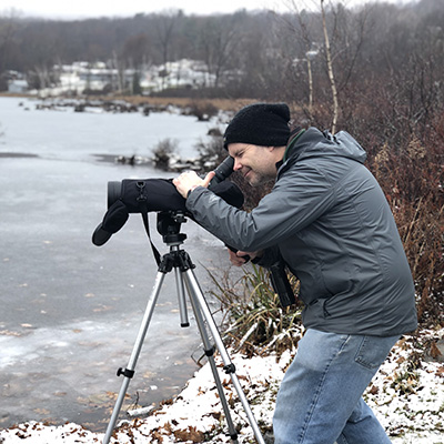 Faculty taking video on a frozen lake